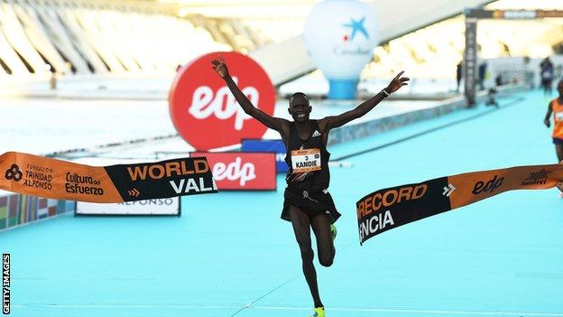 Kibiwott Kandie holding his arms aloft as he crosses the finish line after setting a new world half marathon record