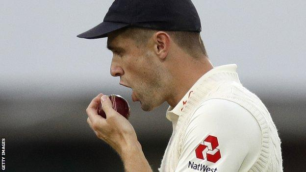 Side on shot of Chris Woakes in England Test kit and cap, holding the ball up in front of his mouth