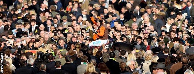 Sam Waley-Cohen on Long Run celebrates amongst race goers after winning the Gold Cup on Long Run at Cheltenham Racecourse