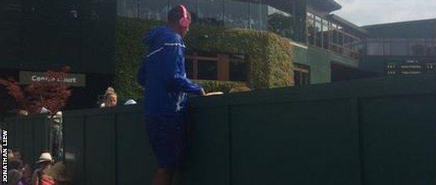 Nick Kyrgios climbing on a railing to watch Hewitt and Kokkinakis in the doubles.