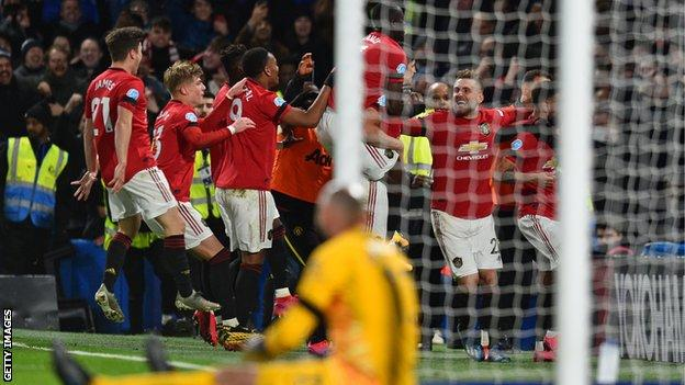 Chelsea keeper Willy Caballero looks on as Manchester United players celebrate