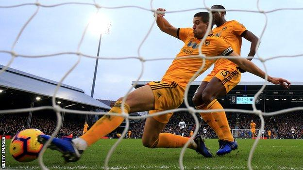 Wolves defender Conor Coady clears the ball off the line against Fulham