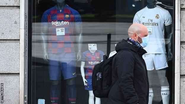 Member of the public wears a mask as he walks past Barcelona and Real Madrid shirts on sale
