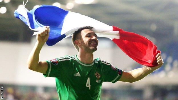 Defender Gareth McAuley celebrates with the French flag after NI beat Greece to qualify for Euro 2016