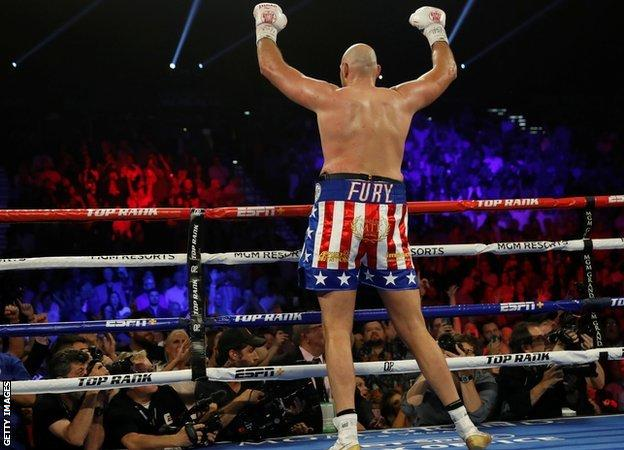 Tyson Fury turns to the crowd to celebrate his win over Tom Schwarz