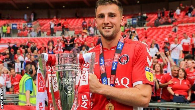 Ben Purrington holds the League One play-off trophy