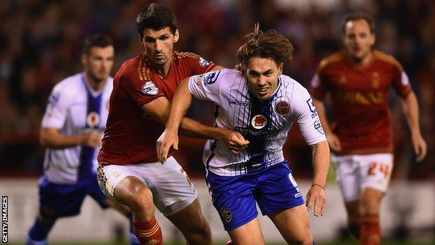 Walsall's hat-trick hero Tom Bradshaw holds off the challenge of Forest's Eric Lichaj