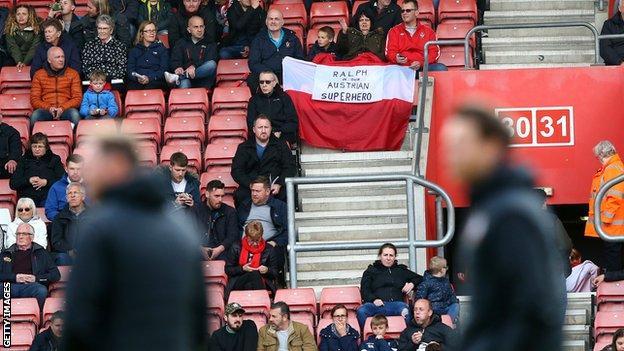 Saints fans hold aloft banner