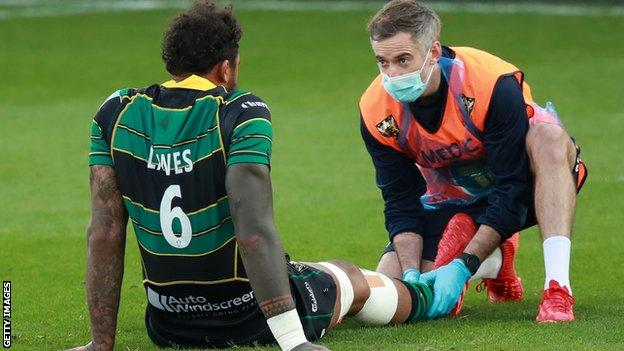 Courtney Lawes receives treatment on the pitch after being hurt against Sale