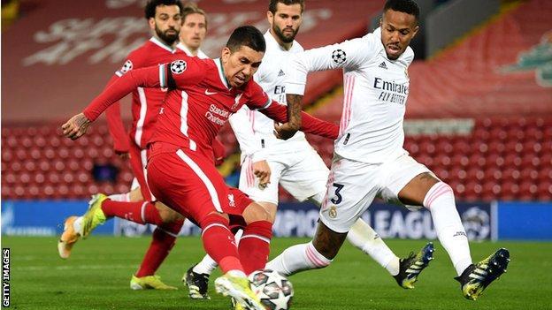 Real Madri's Eder Militao challenges Liverpool's Roberto Firmino
