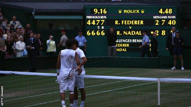 Roger Federer and Rafael Nadal embrace after the 2008 Wimbledon men's singles final, with the scoreboard in the background