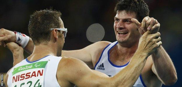 Richard Whitehead hugs teammate Dave Henson after their T42 200m race