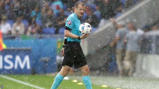 Czech referee Pavel Kralovec leads the players off the pitch after a hail storm
