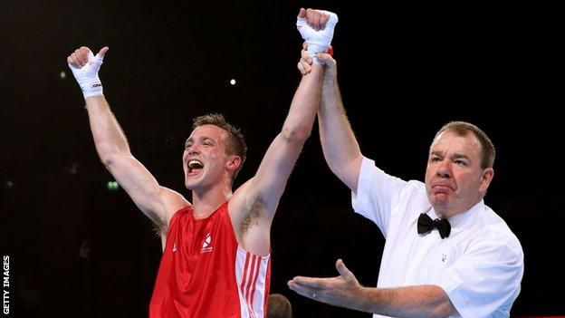 Josh Taylor's arm is raised to signify his win over Junias Jonas of Namibia in the men's 64kg final at Glasgow 2014