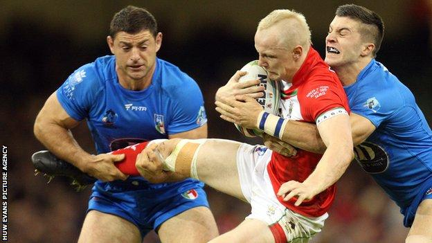 Wales' Rhys Evans is tackled by Italy's James Tedesco in the 2013 Rugby League World Cup