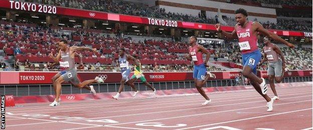 De Grasse (wearing six) and Bednarek (obscured) overhaul Lyles (three) in the final stages of the 200m final