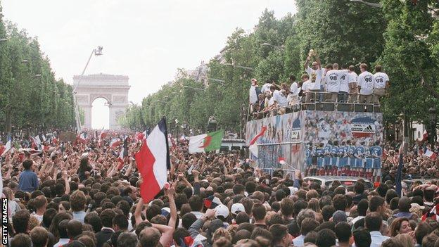 French fans during the parade on the Champs Elysees celebrate the French team's victory
