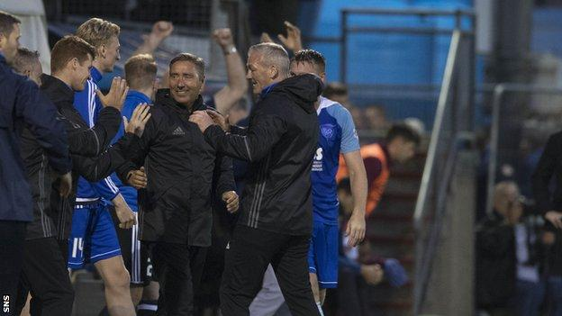 Peterhead boss Jim McInally celebrates at full-time with his bench