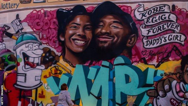 A mourner pays respects at a mural for Kobe Bryant and his daughter in LA