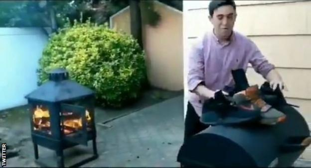 An unknown man burns Nike trainers