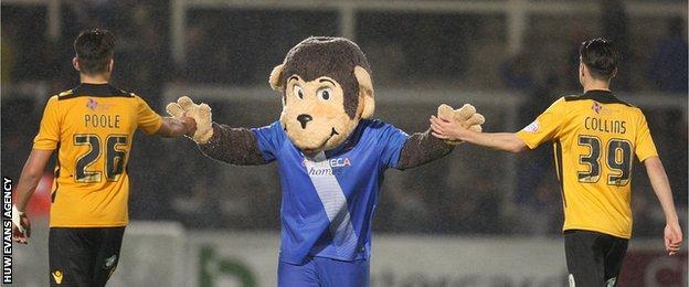 Regan Poole and Aaron Collins high five Hartlepool's monkey mascot