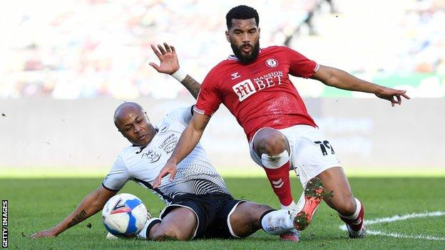 Swansea's Andre Ayew slides in on Adrian Mariappa of Bristol City