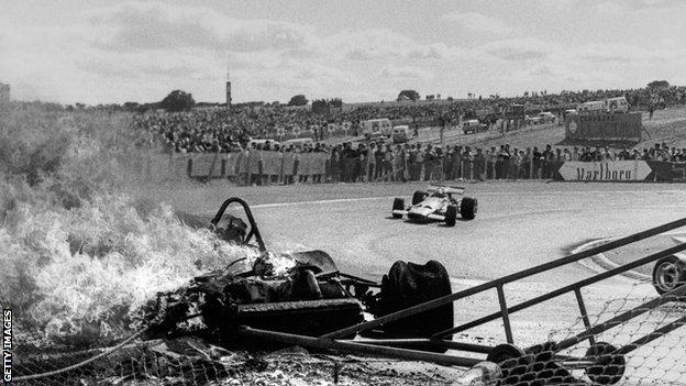 Jacky Ickx, Jochen Rindt, Ferrari 312B, Grand Prix of Spain, Circuito del Jarama, 19 April 1970. Jochen Rindt goes by the burning Ferrari of Jacky Ickx following the first lap accident. (Photo by Bernard Cahier/Getty Images)