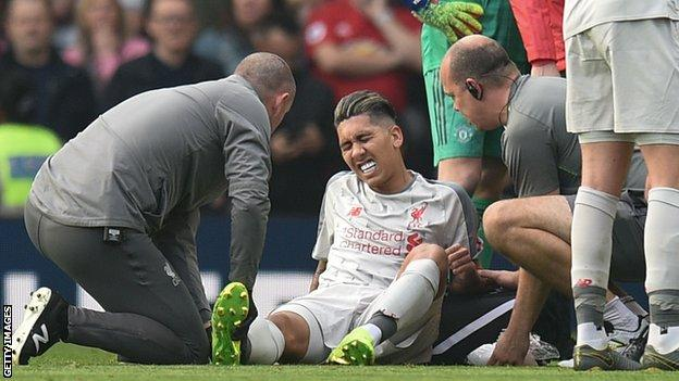 Roberto Firmino receives treatment on the pitch