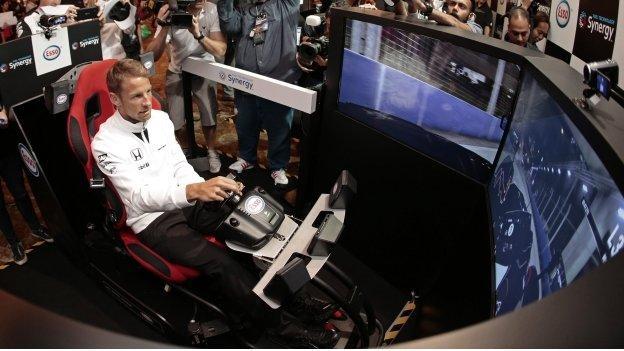 Jenson Button steers a race car stimulator in Singapore