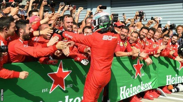 Charles Leclerc celebrates with the Ferrari pit crew