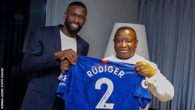 Chelsea's Antonio Rudiger (left) hands over a signed shirt to Sierra Leone President Julius Maada Bio
