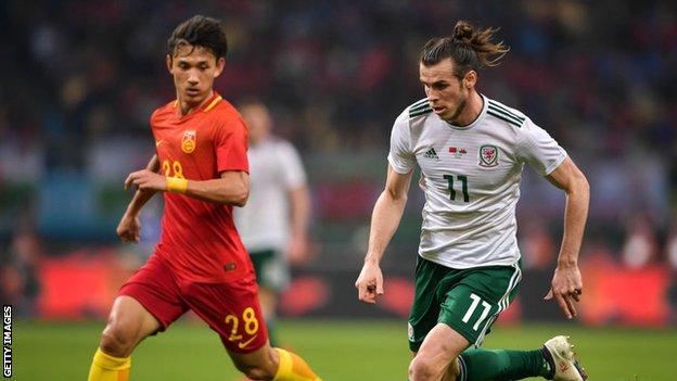 Gareth Bale takes on Wang Shenchao
