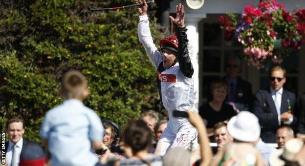 Frankie Dettori performs a flying dismount after winning at Sandown