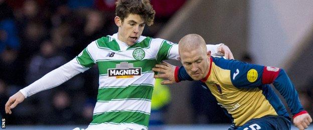 Celtic's Ryan Christie is held off by East Kilbride captain Barry Russell