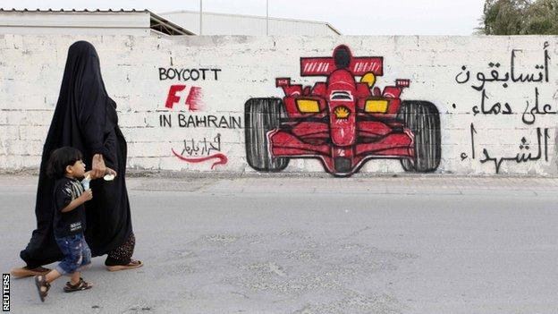 A woman and her child in front of anti-Formula One graffiti in the village of Barbar, Bahrain