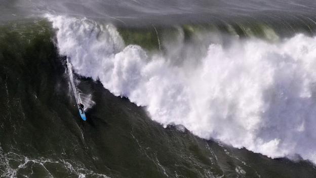 A surfer rides a wave
