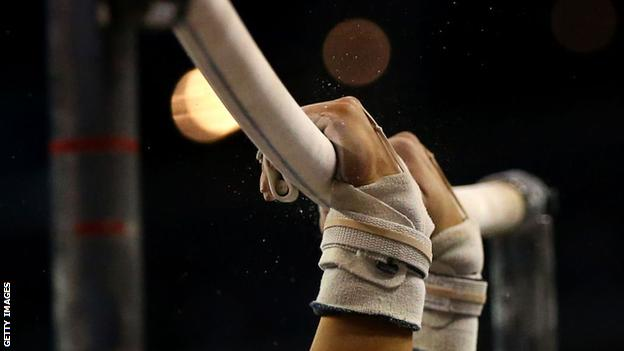 A gymnast's hands on the horizontal bars