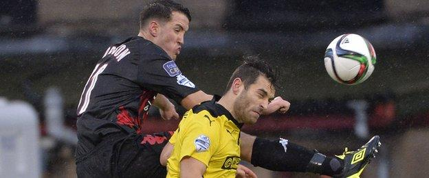 Josh Robinson, who rises high to challenge Cliftonville's David McDaid, could secure a move to England