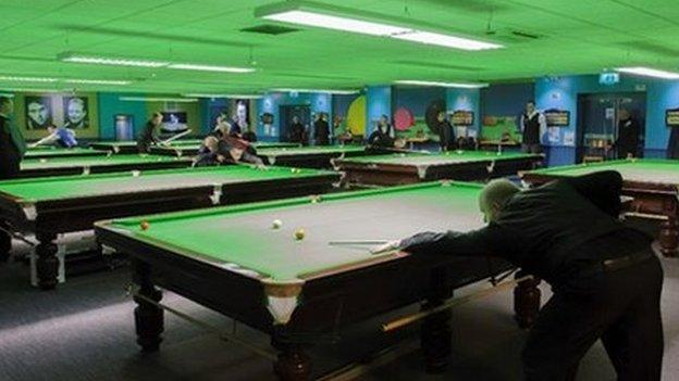 billiards hall with ten tables of players