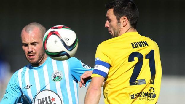 Stephen Hughes of Warrenpoint Town in action against Ballymena United defender Jim Ervin