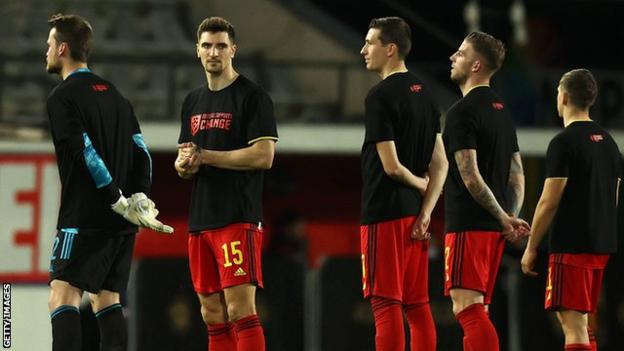 """Belgium's players lined up in T-shirts with the words """"football supports change"""" before kick-off"""