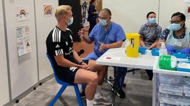 Prof Jonathan Van-Tam prepares to vaccinate Boston United striker Jordan Burrow