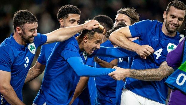 Callum Robinson is congratulated by his team-mates after netting his second goal against Qatar