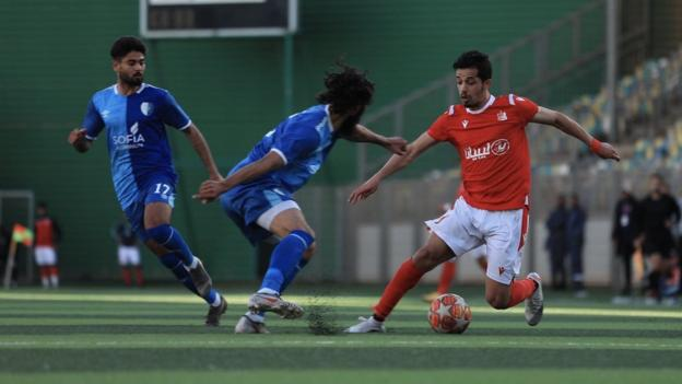Action from Al Ahly Benghazi (in red) against Al Hilal in the Libyan league