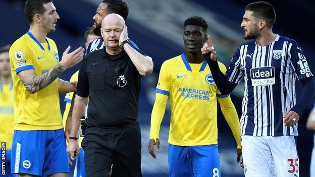 Brighton players with referee Lee Mason
