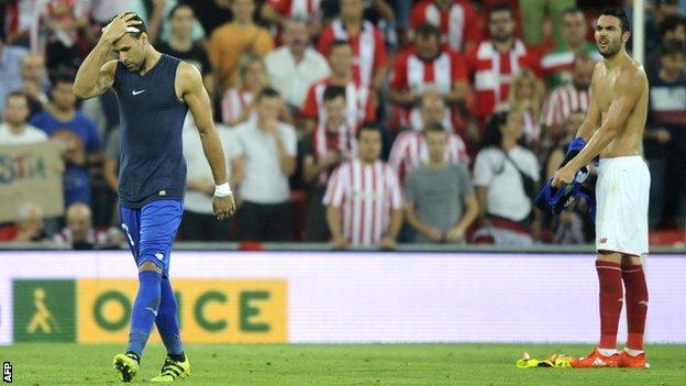 Sevilla keeper Salvatore Sirigu (left) leaves the field as midfielder Vicente Iborra takes over in goal