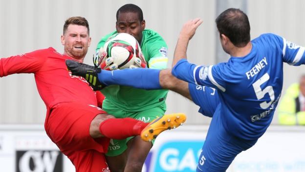 Ballinamallard goalkeeper Alvin Rouse grasps the ball ahead of Portadown's Gary Breen and home defender Stephen Feeney at Ferney Park