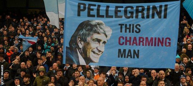 Manchester City fans hold aloft a banner for Manuel Pellegrini