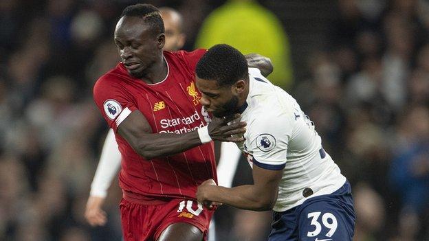 Spurs' Japhet Tanganga (right) tussles with Liverpool's Sadio Mane