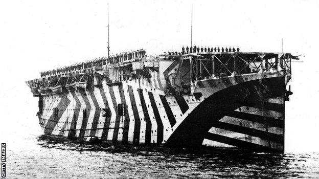 "November 1918: Airmen and seamen cheering King George V from the aircraft carrier ""Argus"" on his visit to the Fleet at Rosyth, on the Firth of Forth. The carrier is painted in ""dazzle"" camouflage, designed to confuse enemy ships - not so much to hide vessels, instead the camouflage was intended to make it difficult to pinpoint the direction in which a ship was travelling."